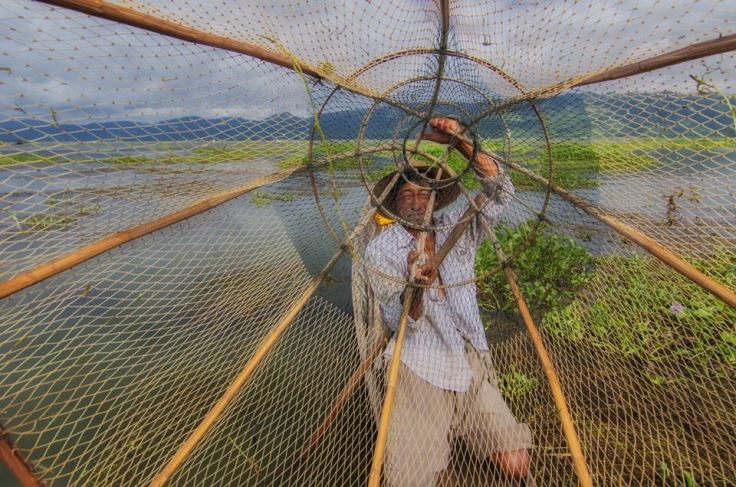 Mr fisherman from Inle Lake. Every fisherman uses their feet to paddle their boat and use their free hands to cast the fishing nets, it becomes a